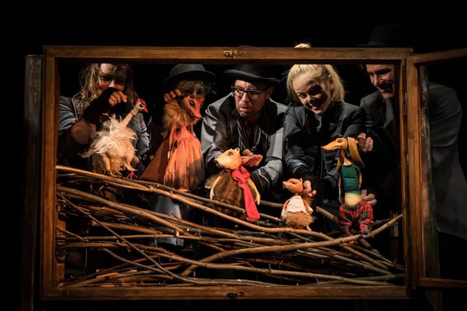 Na zdjęciu widoczne jest drewniane okno. Z okna wyglądają aktorzy, którzy animują lalki.