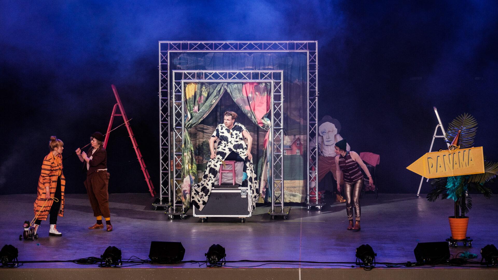 Na zdjęciu widoczny jest scena teatralna. W centralnej części sceny bohater Krowa. Po lewej - bohaterowie - Tygrys i Miś. Po prawej stronie bohater - Kaczka.
