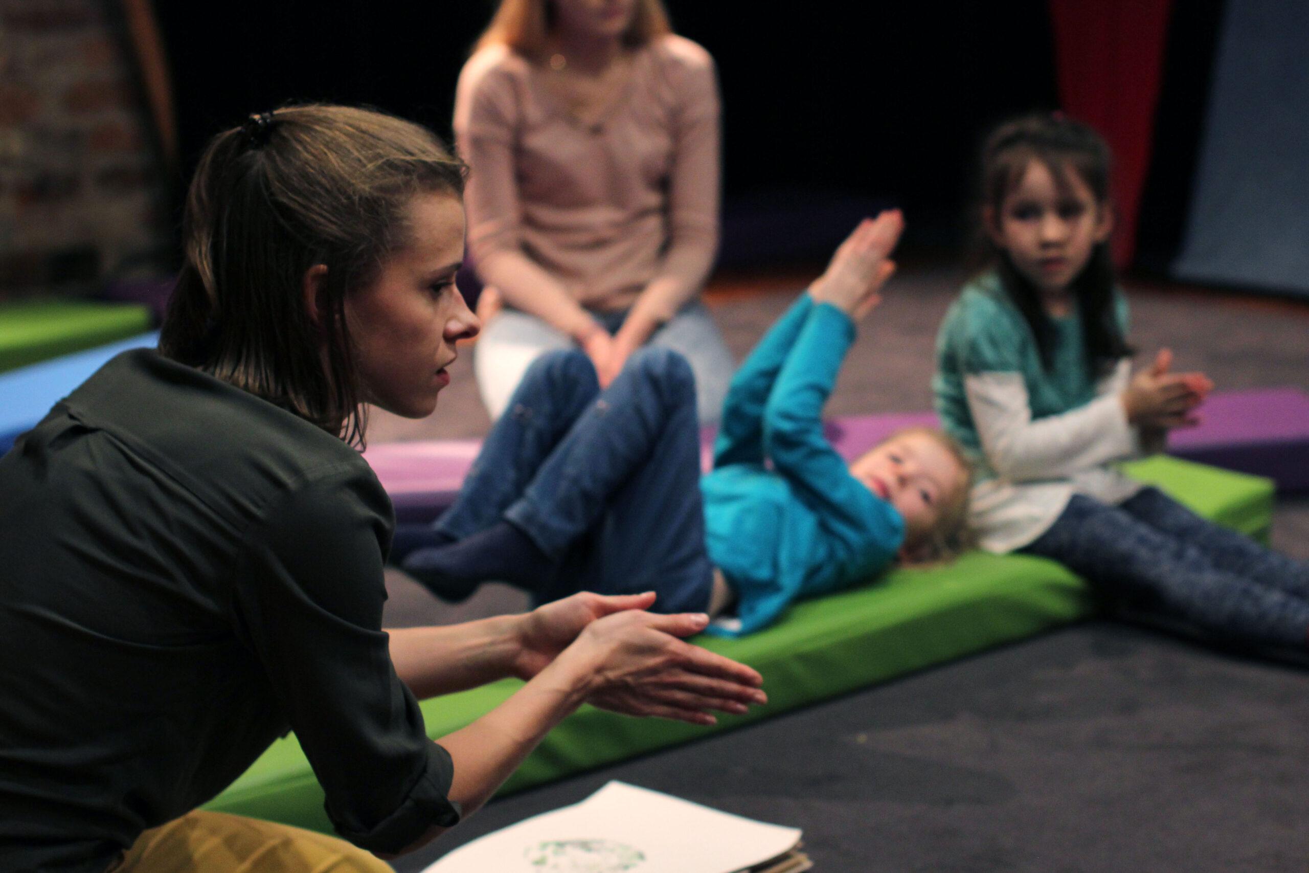 Po lewej stronie zdjęcia znajduje się aktorka rozgrzewająca dłonie. Na prawej stronie zdjęcia znajdują się dzieci powtarzające ruch za aktorką.